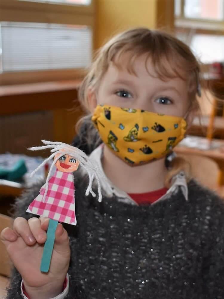 dívka drží loutku z papíru