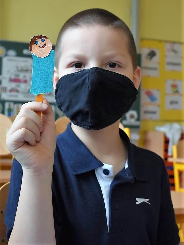 chlapec drží loutku z papíru