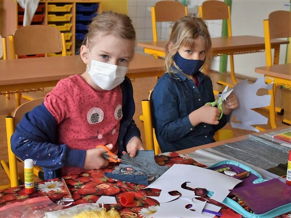 dvě holčičky stříhají papír