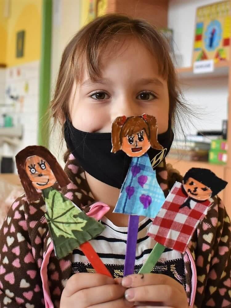 holčička drží loutky členů rodiny